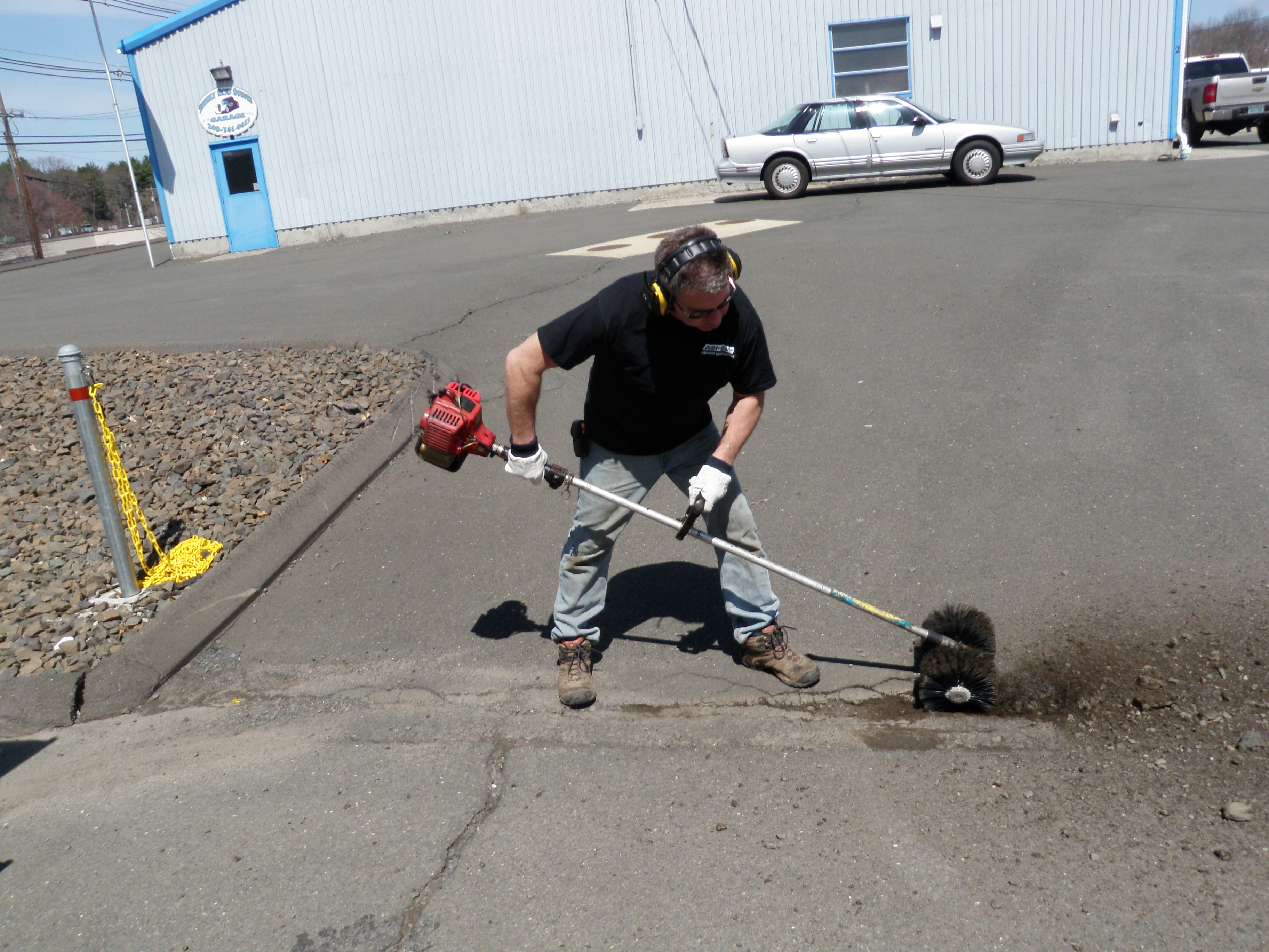 Cleaning Large Crack in Driveway with Power Brush